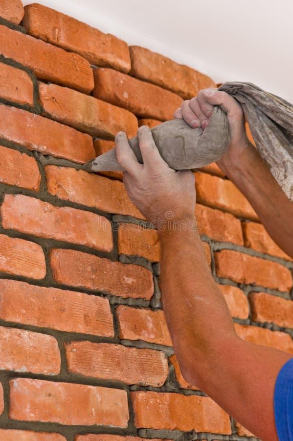 Processus de faire un mur de briques rouge, rénovation à la maison photos libres de droits