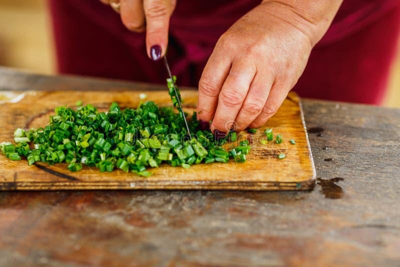 Processus de faire une salade fraîche, coupant le jeune oignon vert sur le conseil en bois photographie stock