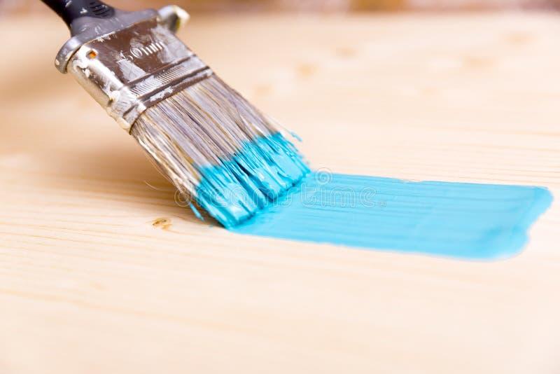 Processus de peindre le conseil en bois avec la brosse et le turquo photographie stock libre de droits