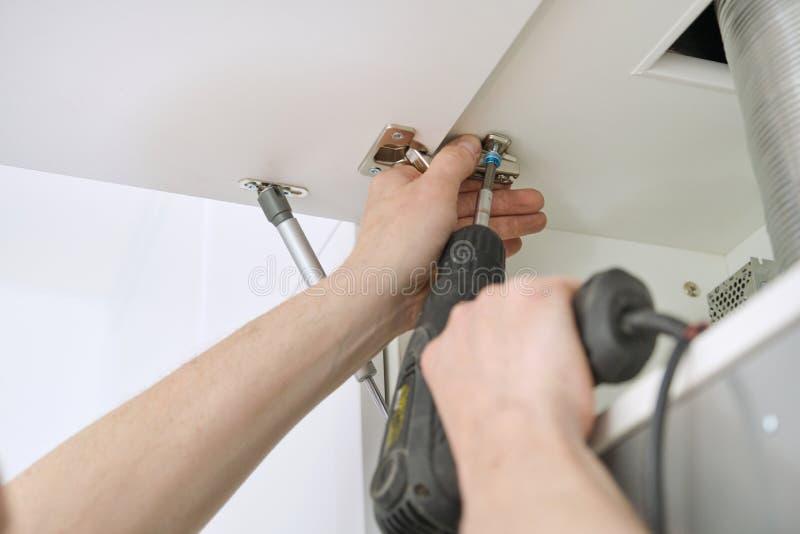 Processus de plan rapproché d'assembler les meubles de cuisine, mains du travailleur de sexe masculin avec les outils professionn images libres de droits