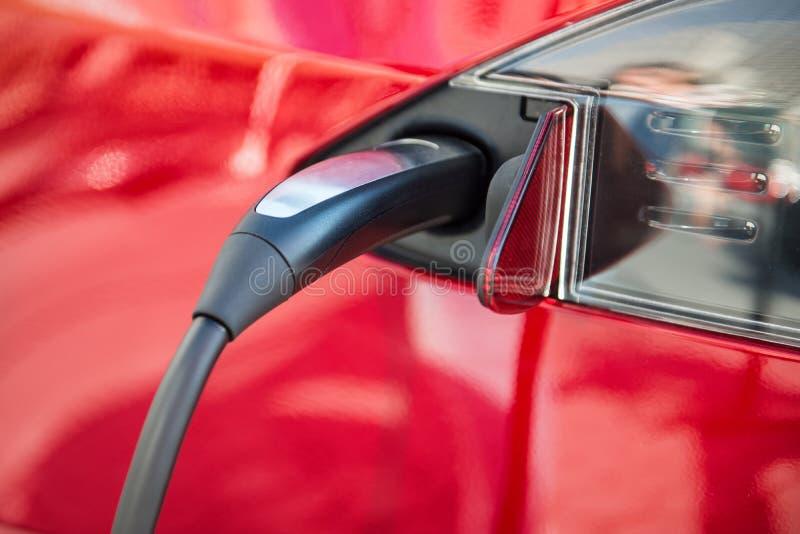 Processus de remplissage de voiture électrique par l'offre de cable électrique branchée photos stock