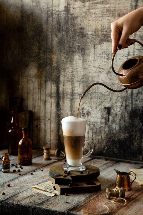 Processus de verser le café dans les supports en verre de latte sur les conseils en bois sur la table rustique grise photos stock