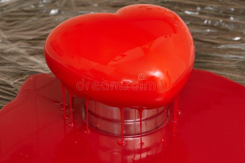 Processus de verser le lustre rouge sur le gâteau de forme de forme de coeur images libres de droits
