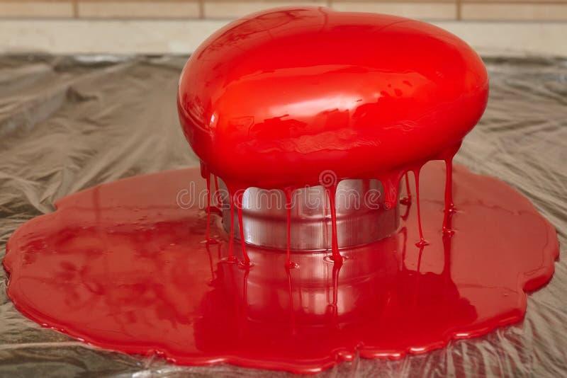 Processus de verser le lustre rouge sur le gâteau de forme de forme de coeur photographie stock