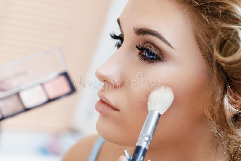 Processus fonctionnant appliquant le maquillage sur le visage d'une fille image stock