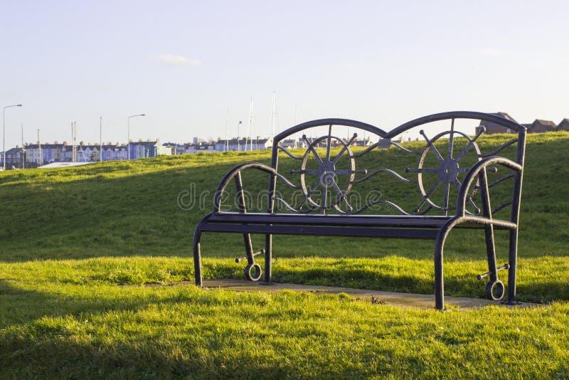 Prochowego pokrytego metalu parkowa ławka w współczesnym projekcie backlit z miękkim światłem zimy słońce zdjęcie stock