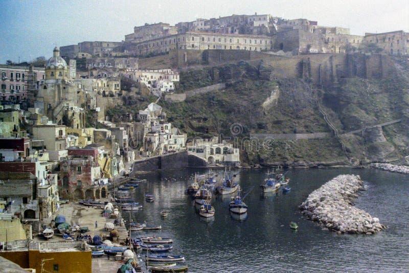 PROCIDA, ITALIE, 1975 - la vieille prison de Procida domine Marina di Corricella avec ses bateaux de pêche images libres de droits