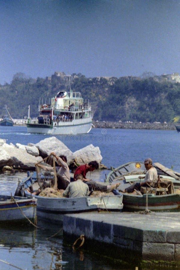 PROCIDA, ITALIE, 1975 - pêcheurs au travail réparant leurs filets de pêche tandis que le ferry part du port photo libre de droits