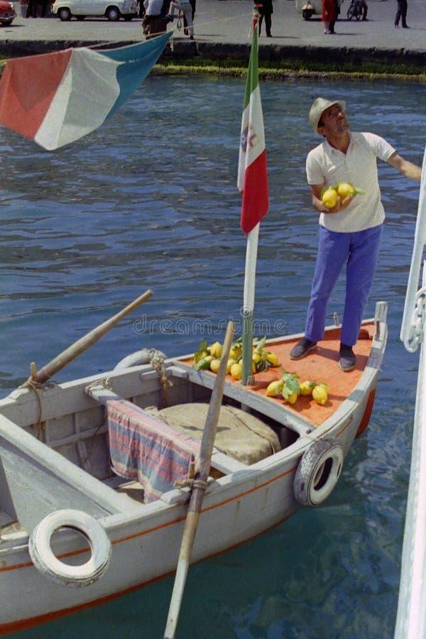 PROCIDA ITALIEN, 1974 - båtuthyraren säljer Procida citroner till turister på färjan som ankras i porten direkt av hans eka, arkivfoton
