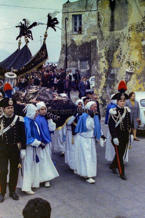 PROCIDA ITALIEN, 1974 - Carabinieri i hög enhetlig eskort statyn av den döda Kristus under långfredagprocessionen royaltyfri bild