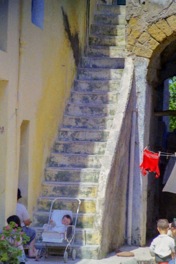 PROCIDA, ITALIEN, 1979 - ein Baby schläft friedlich in seinem Rollstuhl am Fuß eines Treppenhauses stockfotos