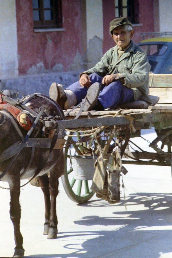 PROCIDA ITALIEN, 1976 - en gamal man observerar med kuriositet och uppmärksamhet från hans vagn royaltyfri fotografi