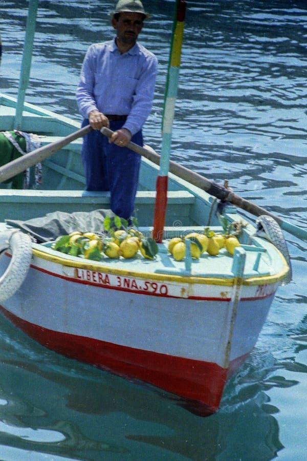 PROCIDA ITALIEN, 1979 - en man säljer citroner från hans fartyg i porten av Procida arkivfoton
