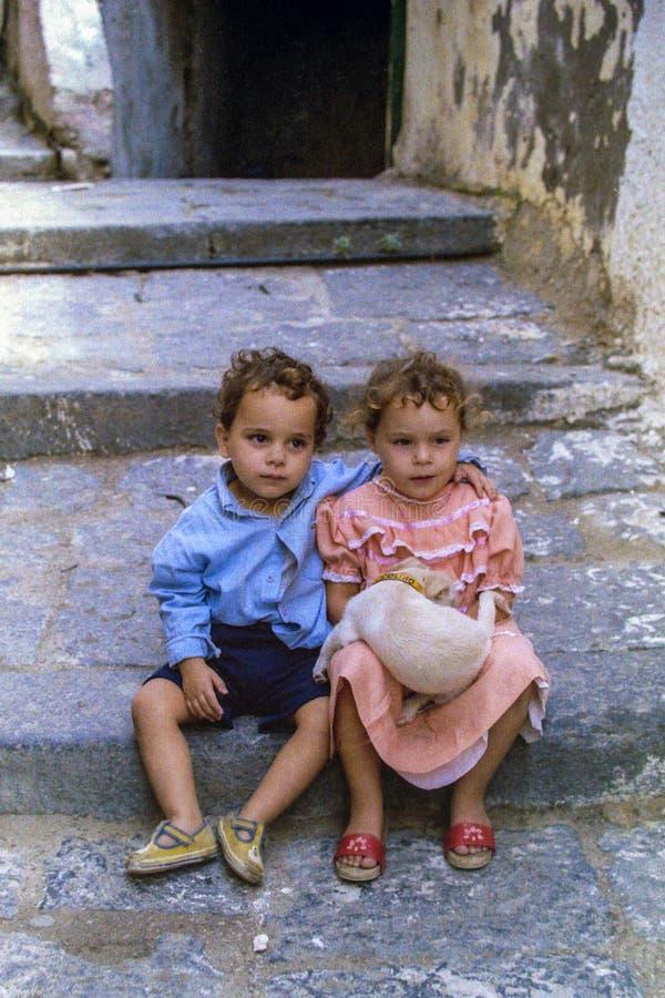 PROCIDA ITALIEN, 1978 - ett barn med hans arm skyddar lovingly hans syster som rymmer lite hunden på hennes varv royaltyfria bilder