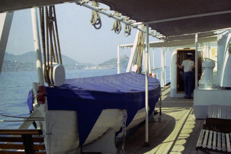 PROCIDA ITALIEN, 1975 - skepp för ett räddningsaktionfartyg på en färja mellan Procida och Pozzuoli med bakgrunden av den Phlegre arkivfoton