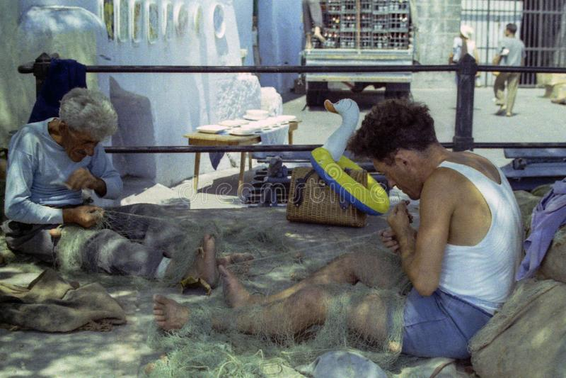 PROCIDA ITALIEN, 1972 - två fiskare att reparera deras fisknät med expertis och erfarenhet arkivbilder