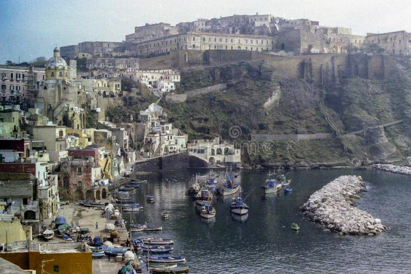 PROCIDA, ITALY, 1975 - The old Procida prison dominates the Marina di Corricella with its fishing boats royalty free stock images