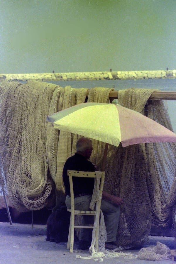 PROCIDA, WŁOCHY, 1975 - rybak naprawia jego sieci rybackie na molu w cieniu parasol obraz royalty free