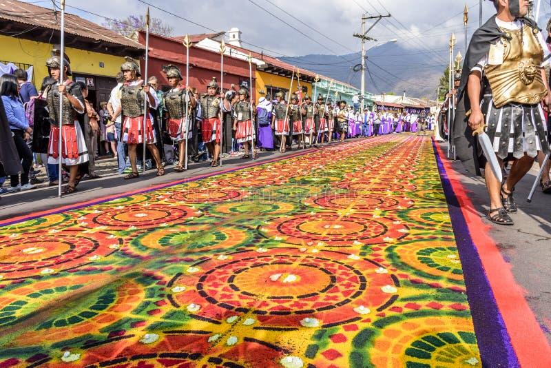 A procissão do Sexta-feira Santa anda ao lado dos tapetes tingidos da serragem, Antígua, Guatemala imagens de stock royalty free