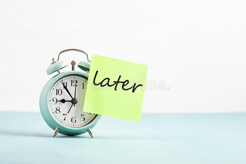 Procrastination, delay concept. Bad time management. Word later sticked to alarm clock stock image