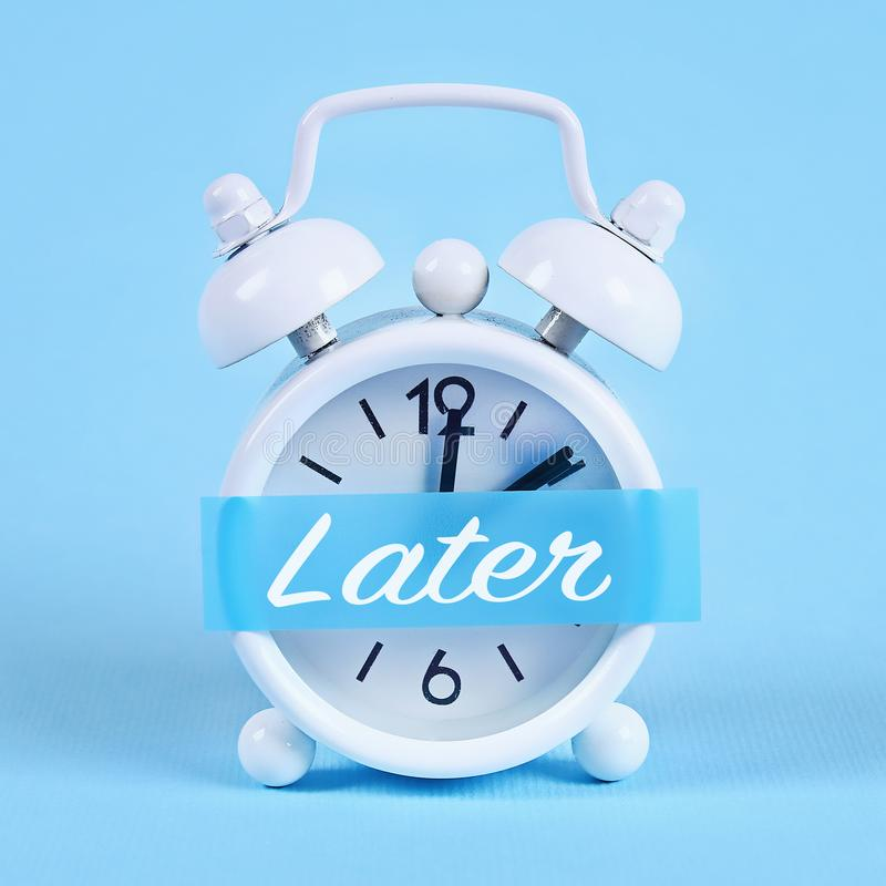 Procrastination, delay, urgency concept. White alarm clock with a sticky note with text later. Procrastination, delay and urgency concept. White alarm clock with royalty free stock photo