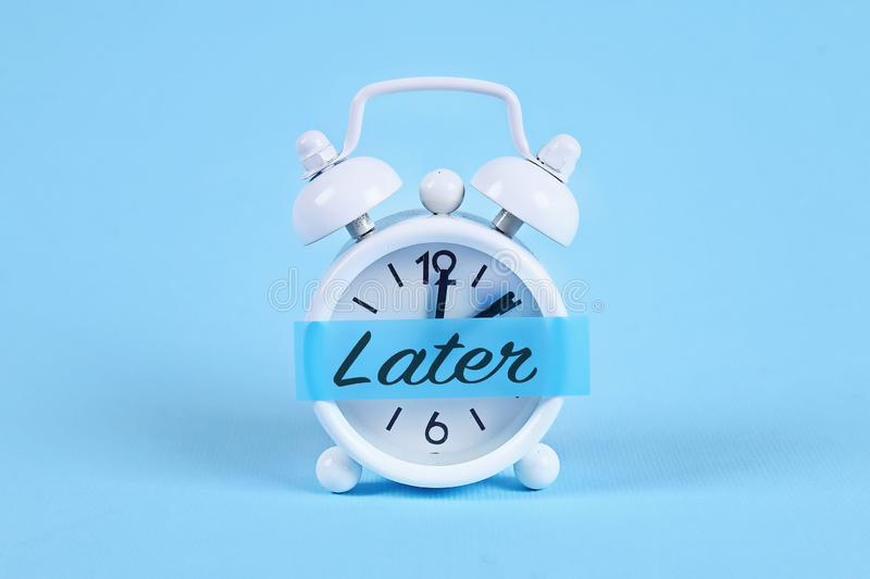 Procrastination, delay, urgency concept. White alarm clock with a sticky note with text later. Procrastination, delay and urgency concept. White alarm clock with royalty free stock photography