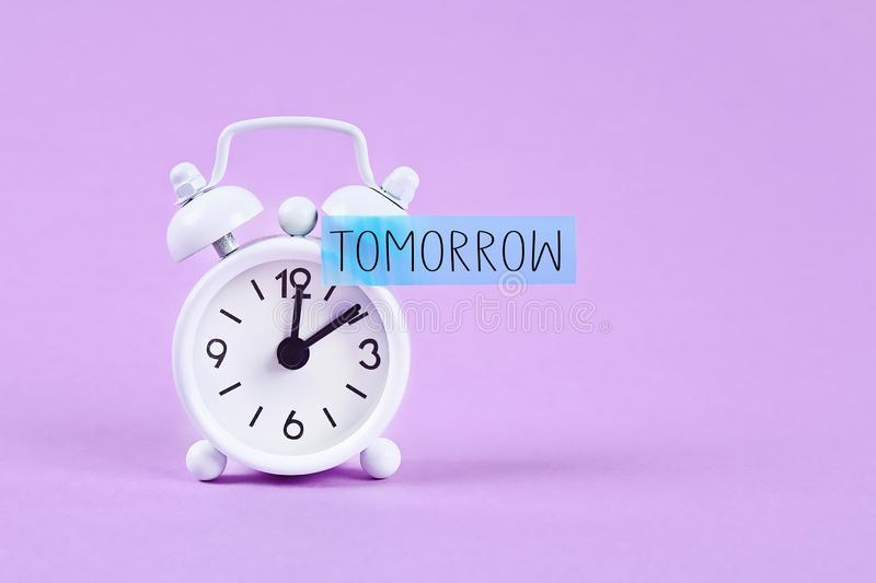 Procrastination, delay, urgency concept. White alarm clock with a sticky note with text tomorrow. Procrastination, delay and urgency concept. White alarm clock royalty free stock photo