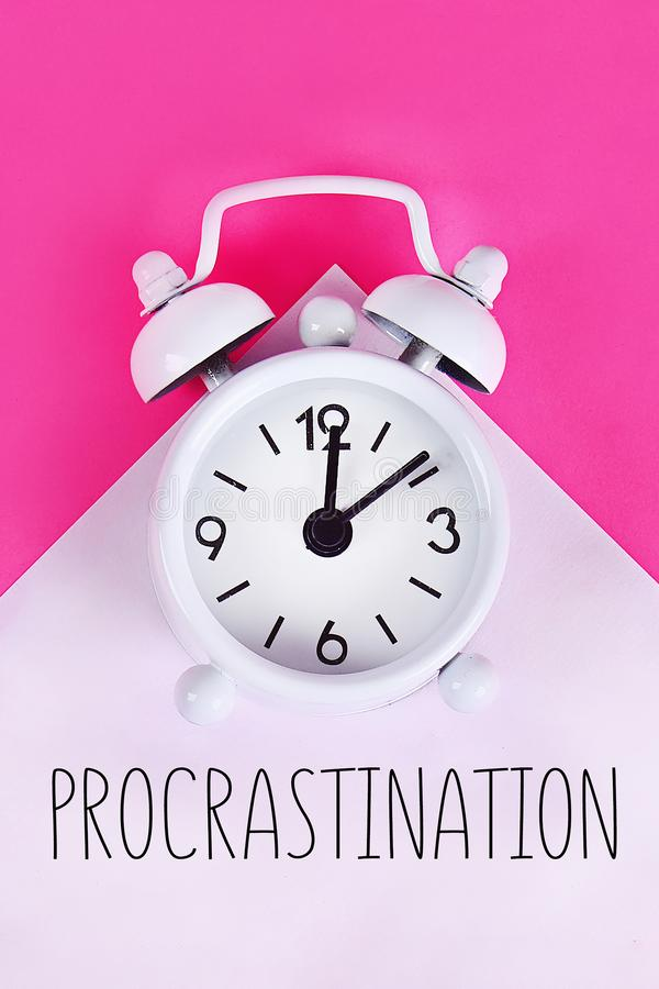 Procrastination, delay, urgency concept. White alarm clock with text procrastination. Procrastination, delay and urgency concept. White alarm clock with text stock photography