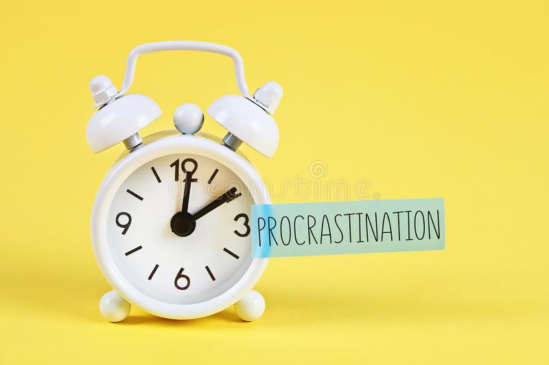 Procrastination, delay, urgency concept. White alarm clock with text procrastination. Procrastination, delay and urgency concept. White alarm clock with text royalty free stock photo