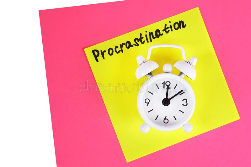 Procrastination, delay, urgency concept. White alarm clock with text procrastination. Procrastination, delay and urgency concept. White alarm clock with text stock images