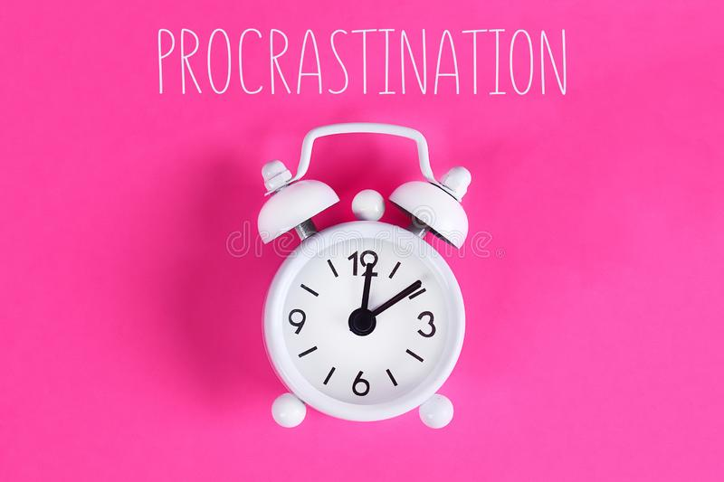 Procrastination, delay, urgency concept. White alarm clock with text procrastination. Procrastination, delay and urgency concept. White alarm clock with text royalty free stock image