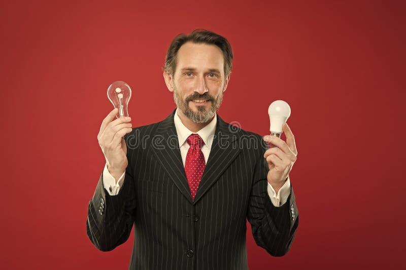 Procurando ideias novas Economia de poder Homem no equipamento do neg?cio Homem de neg?cios na ampola da posse do terno Eletricid imagens de stock