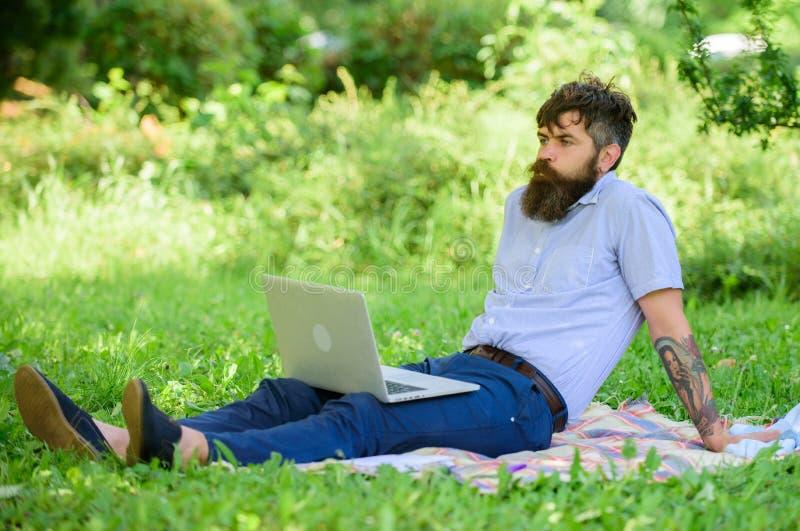 Procurando a inspiração Homem farpado com fundo de relaxamento da natureza do prado do portátil Blogger que torna-se inspirado po foto de stock