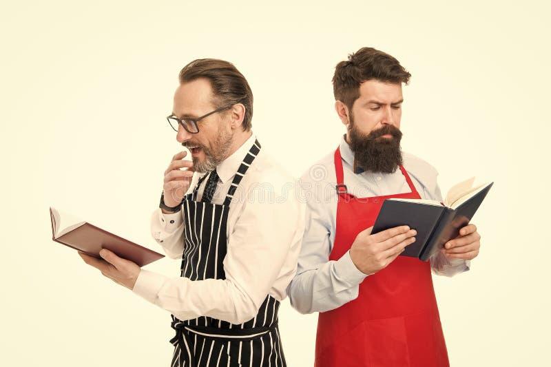 Procurando a melhor receita r Receitas do livro i Cozinheiros chefe farpados dos homens com livros ou fotos de stock royalty free