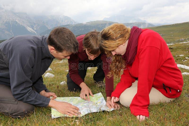 Procurando o destino em um mapa nas montanhas fotos de stock