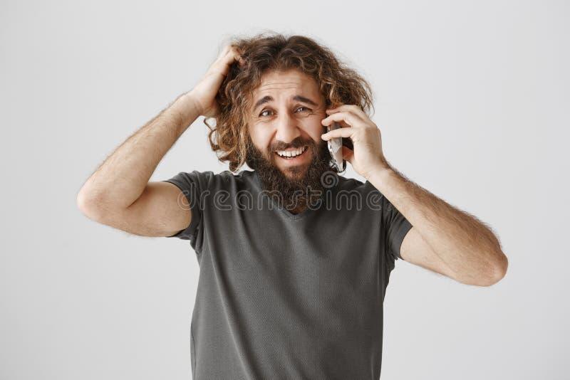 Procuras dos clientes impossíveis Retrato do empresário oriental confundido e incomodado que fala no smartphone e no risco imagens de stock