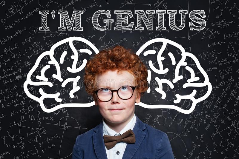 Prodigy child boy with curly ginger hair in glasses. Genius kid royalty free stock photos