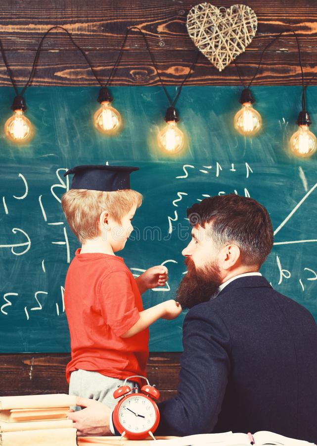 Prodigy child concept. Teacher with beard, father teaches little son in classroom, chalkboard on background. Boy, child. In graduate cap discussing scribbles on stock image