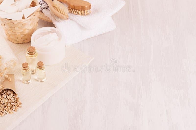 Prodotti bianchi dei cosmetici della stazione termale rustica naturale tradizionale ed accessori beige del bagno su fondo di legn fotografia stock