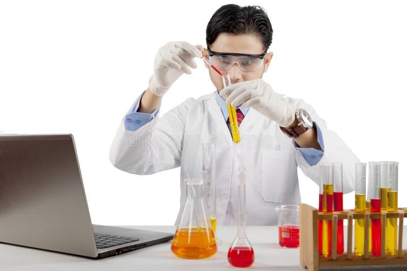 Prodotti chimici maschii di miscelazione dello scienziato isolati sopra fondo bianco fotografia stock