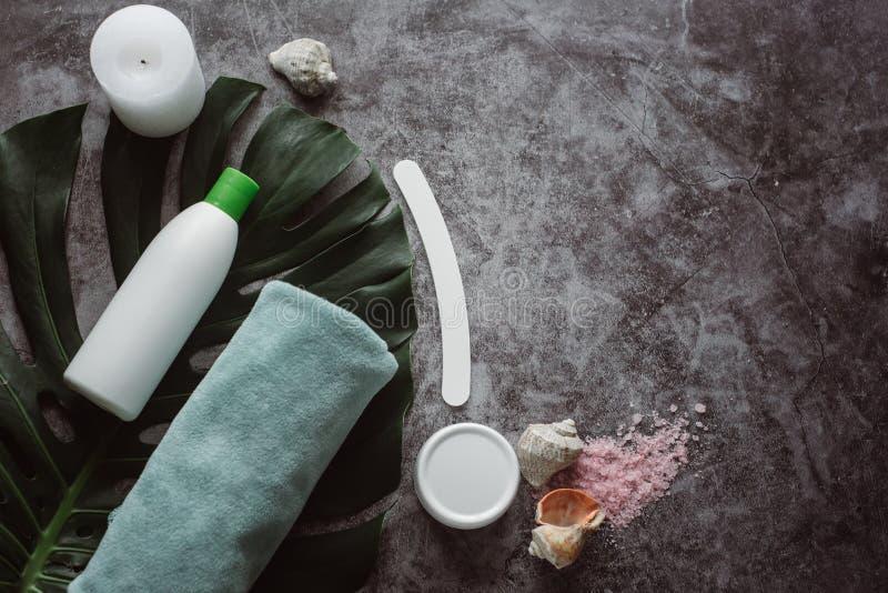 Prodotti cosmetici bianchi e foglia verde su fondo concreto grigio fotografia stock libera da diritti