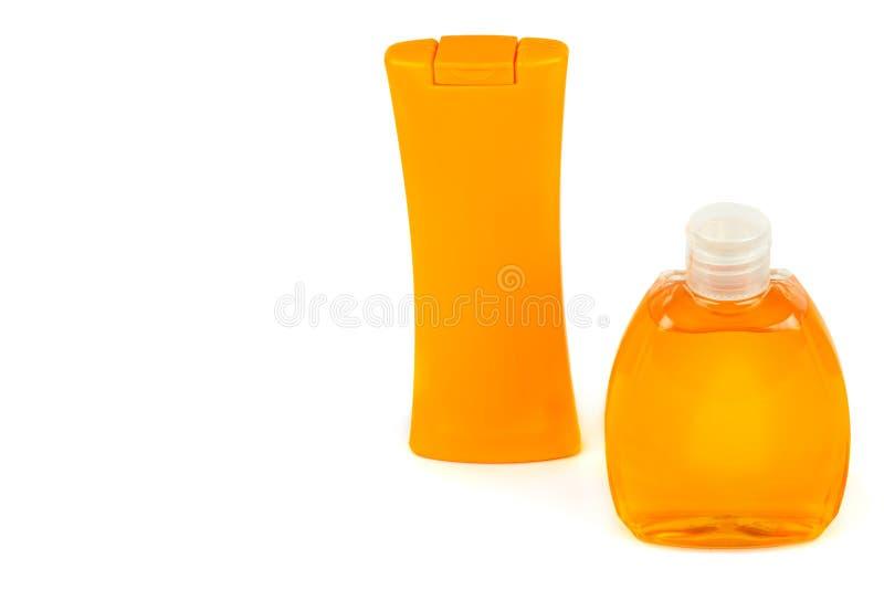 Prodotti cosmetici naturali arancio: Lozione solare e lozione Fiale isolate su fondo bianco Spazio libero per testo fotografia stock
