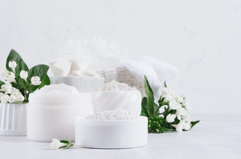 Prodotti delicati dei cosmetici della luce di eleganza per cura di pelle e del corpo con i fiori bianchi e le foglie verdi fresch immagine stock