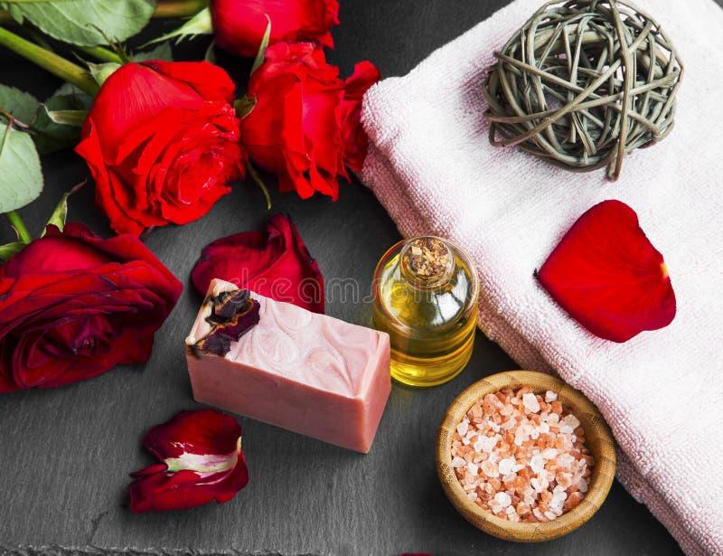 Prodotti della stazione termale con il petrolio, il sapone ed il sale marino di rose Rose rosse immagine stock libera da diritti