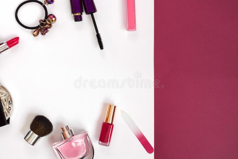 Prodotti di bellezza cosmetici che si rovesciano fuori sopra ad un fondo colorato pastello, con spazio vuoto sul lato immagini stock