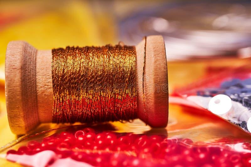Prodotti e strumenti del ricamo La bobina del filo metallico, delle perle giapponesi del seme e degli zecchini su un fondo giallo fotografia stock libera da diritti