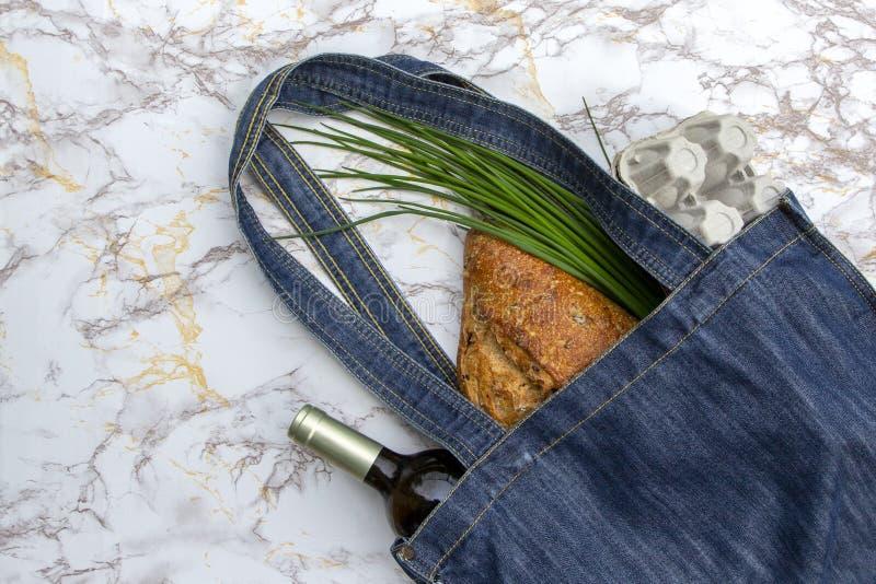 Prodotti freschi nella borsa blu del mercato del denim sul fondo di marmo del tavolo da cucina, disposizione piana Sacchetto dell fotografia stock libera da diritti