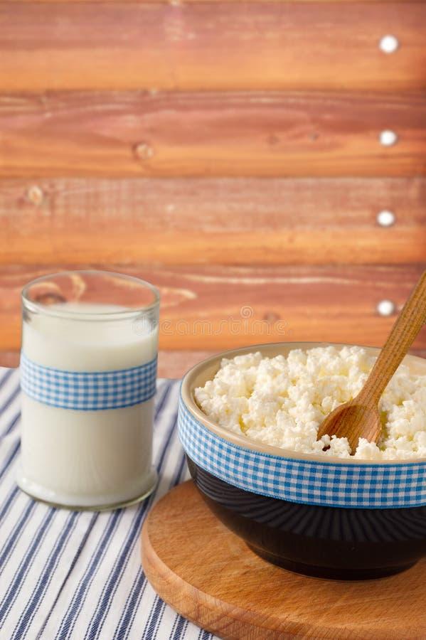 Prodotti lattier-caseario: latte e ricotta con il cucchiaio di legno su Lin fotografia stock