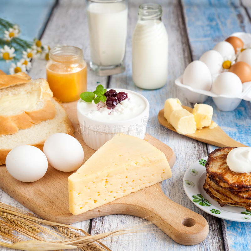 Prodotti lattier-caseario, pancake, miele ed uova fresche immagine stock libera da diritti