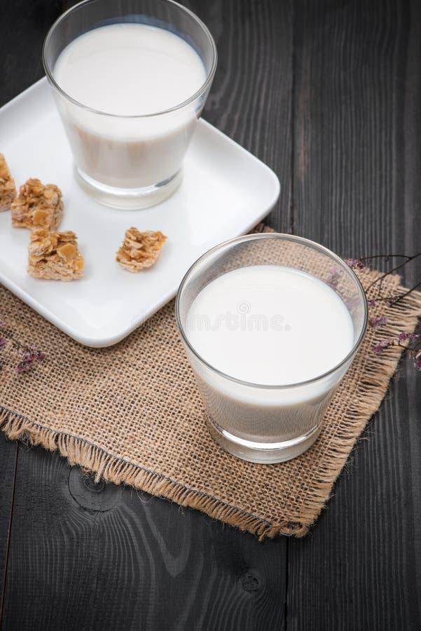 Prodotti lattier-caseario Un servire del bicchiere di latte con le caramelle della mandorla su una r fotografia stock